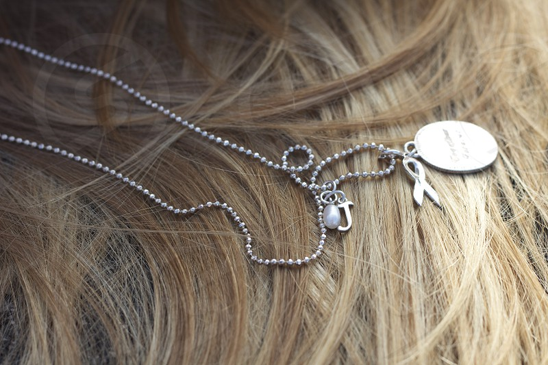 silver round pendant necklace on brown human hair photo