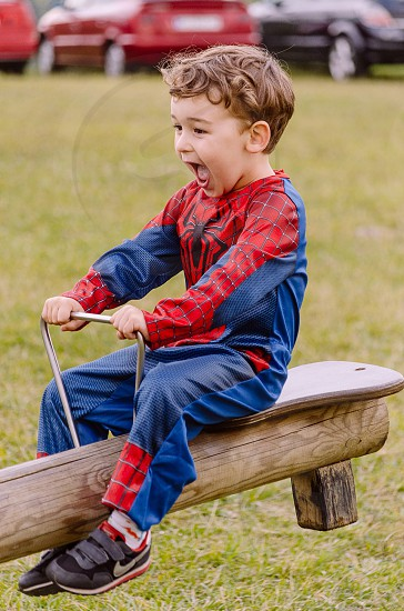 boy in spider man costume in see saw photo