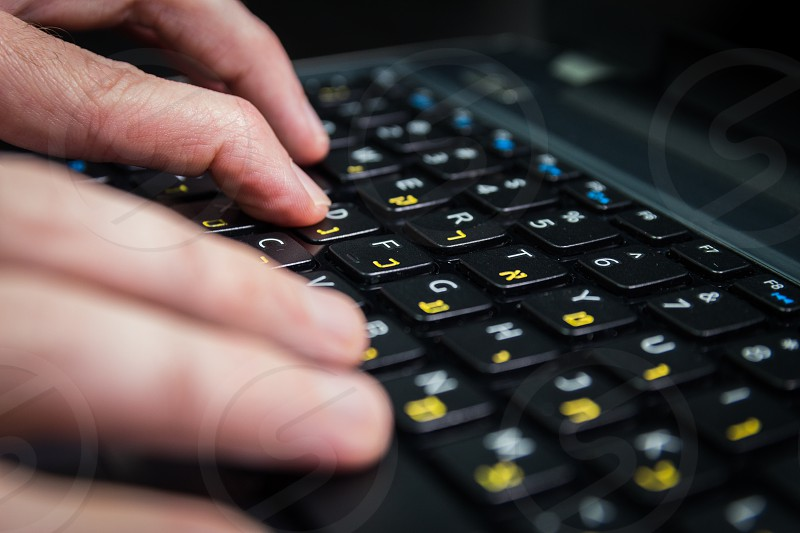 Man typing on a keyboard with letters in Hebrew and English - Laptop keyboard - Close up_Dark atmosphere photo