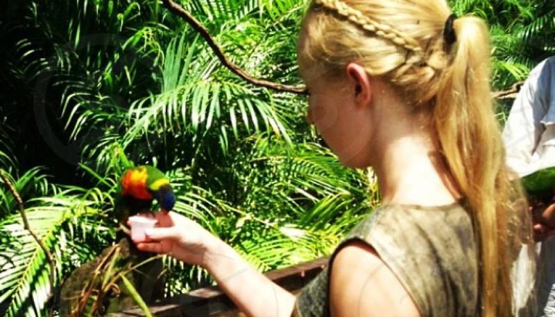 woman in brown tank top dress feeding bird photo
