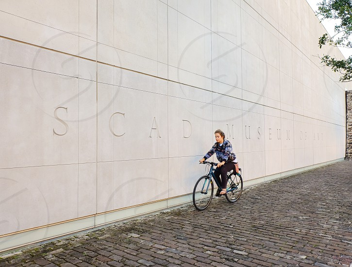 Young girl cycling by the wall of SCAD Museum of Art in Savannah Georgia USA. photo