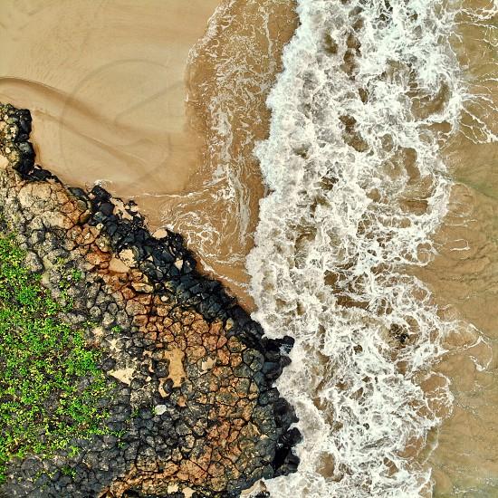 Minimalist aerial beach rock water drone sand black Maui Hawaii  photo