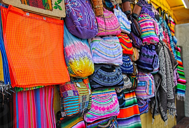 Colorful woven bags and pouches hang on a cart in a street market photo