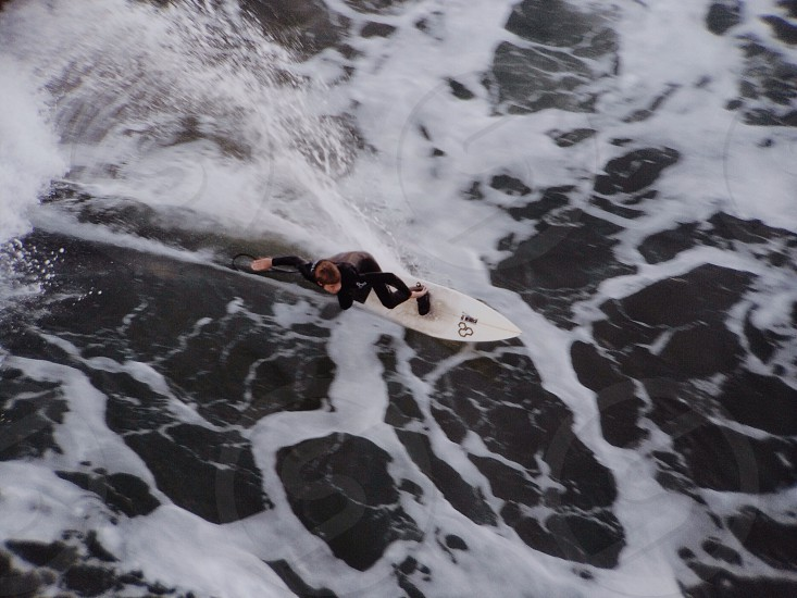 man in black suit riding on surfboard photo