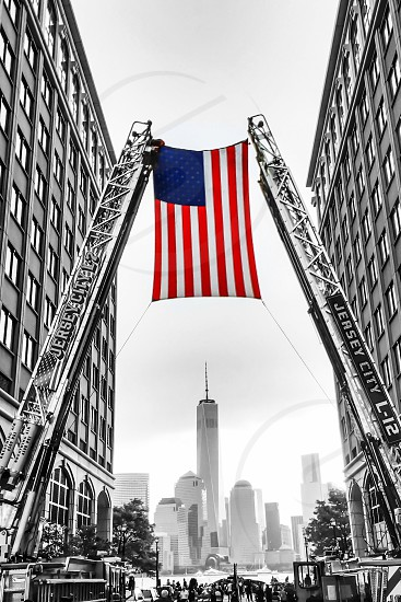 selective color photo of USA flag being raised with view of Freedom Tower in New York photo