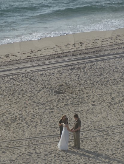 Couple exchanging vows on a beach by the ocean. photo