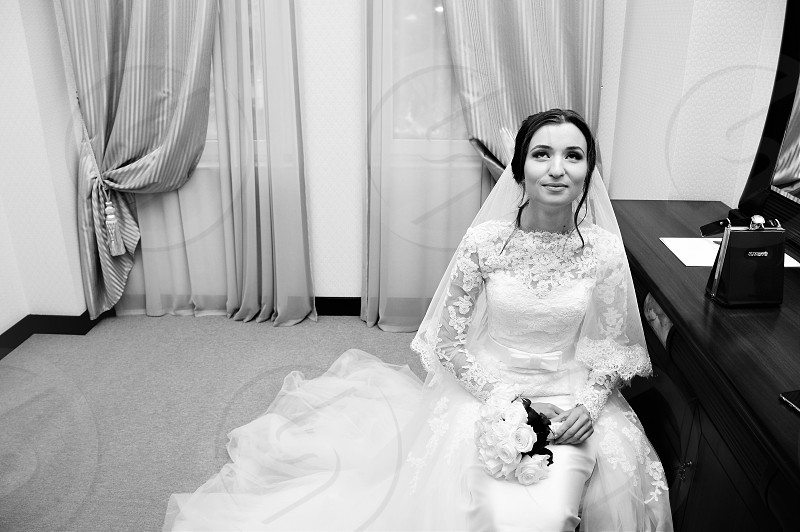 grayscale photo of woman wearing floral turtle neck lace elbow sleeve wedding gown holding bocquet of flower while sitting on bed beside vanity dresser inside room photo