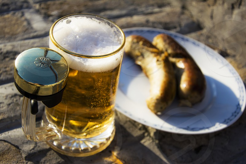 Mug of beer with ring bell on it and sausages on a plate on the street photo