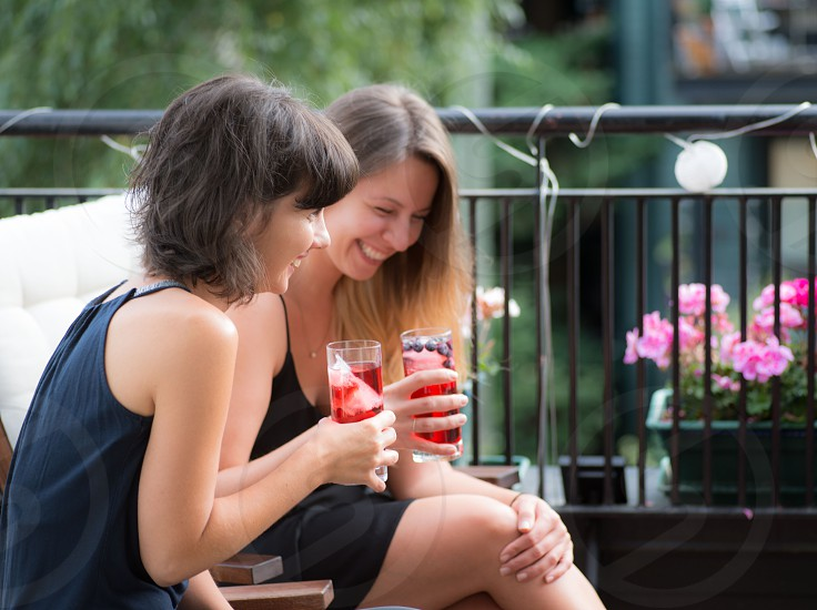 2 smiling women in black dresses holding drinking glasses on balcony during daytime photo