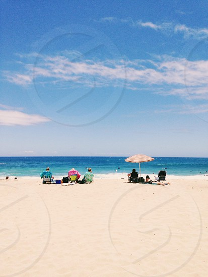 people sitting on the ground with white beach umbrella on white sand under blue skies photo