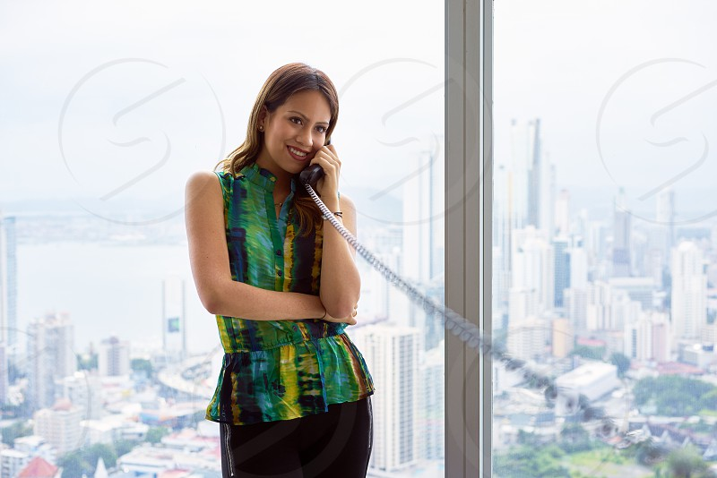woman work businesswoman phone wire telephone modern office adult attractive beautiful business businessperson call calling casual cheerful city communications conversation copy space corporate emotions employee enjoy expression female fun happy hispanic holding internet joy leaning lifestyle people person sight skyscraper smile smiling standing window wired worker working workplace young photo