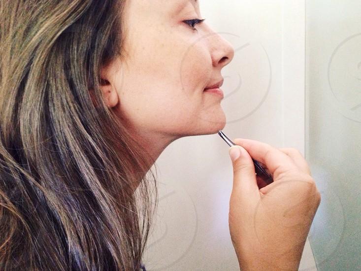 woman pulling chin hair photo