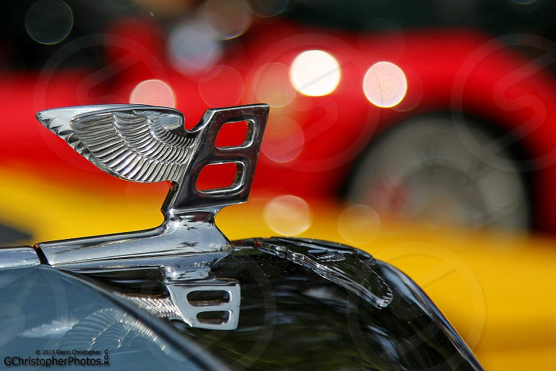 A Bentley hood ornament with a red background.  photo