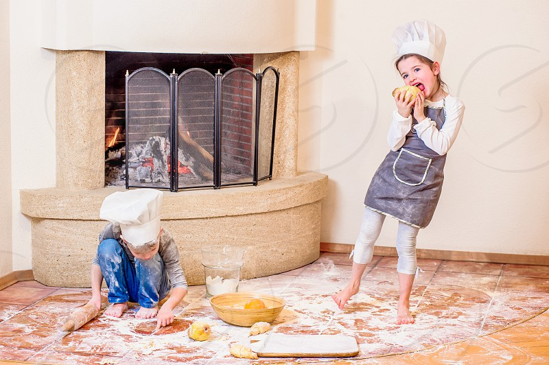 Two cute kids - boy and girl - in chef's hats near the fireplace sitting on the kitchen floor soiled with flour playing with food making mess and having fun photo