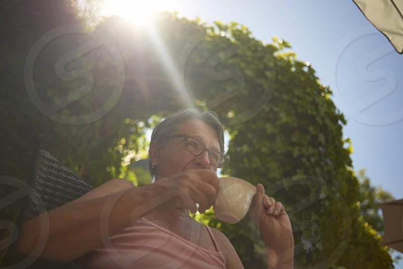 Affluent elderly woman sitting in her back garden enjoying the summer sunshine drinking coffee photo