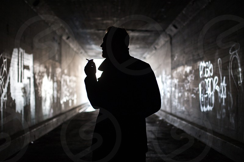 Silhouetted man in tunnel smoking cigarette. photo