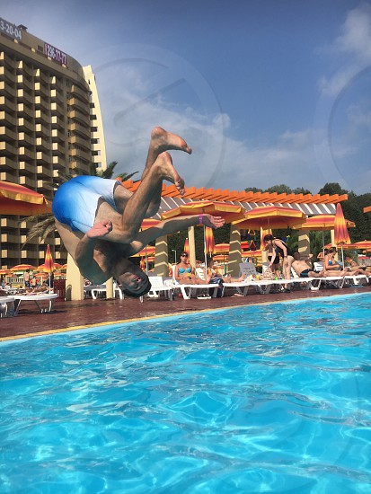 man jumping on pool with people on side sitting on white plastic loungers in front of commercial building photo