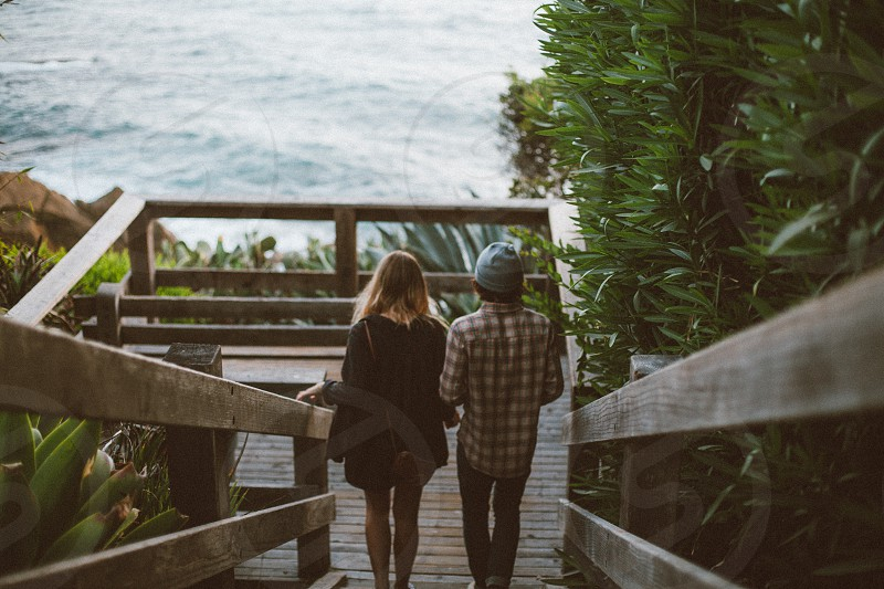 couple on lower portion portion of staircase near sea during daytime photo