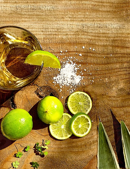 Looking down at tequila glass limes slakt agave and clovers on a wooden table photo