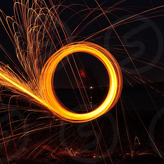 long exposure low light time lapse light painting photo of person using fireworks during nighttime in the dark photo