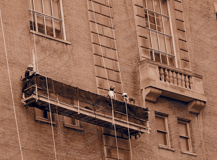 people working on side of building photo