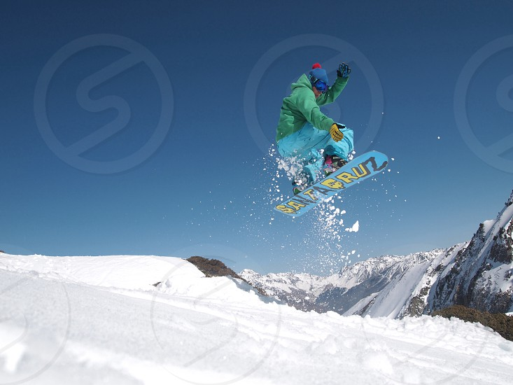person wearing green jacket doing snowboard stunt under clear blue sky at daytime photo