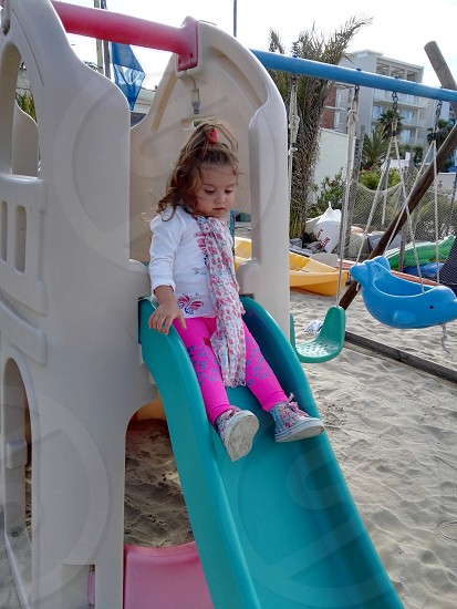 girl in white top and pink pants playing in green brown slide photo