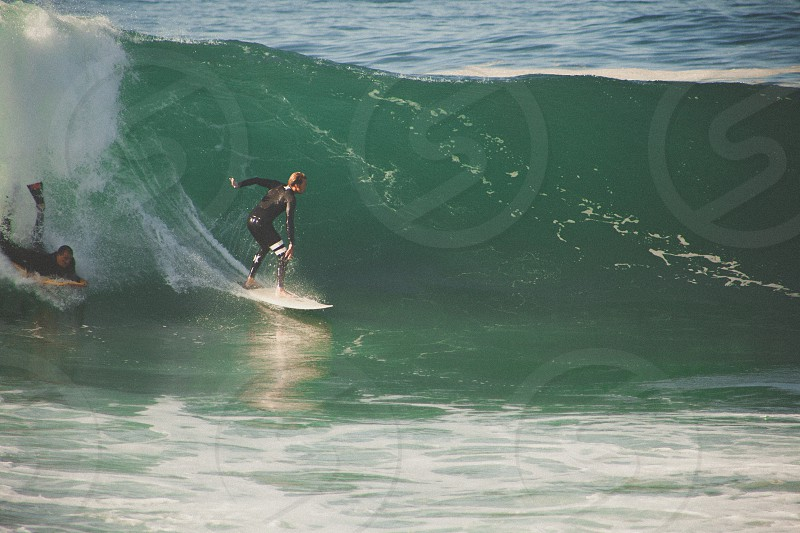 person in black wet suit surfing followed by another person lying on white surfboard on green large wave of sea water during daytime photo