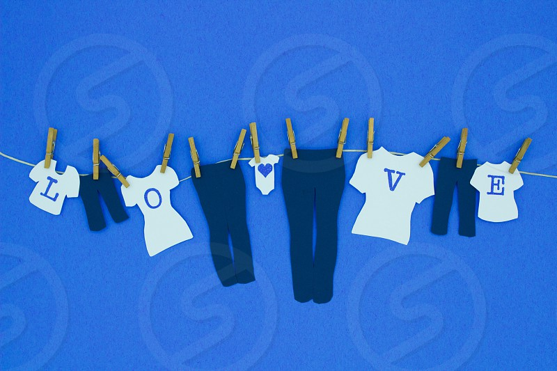 """Modern Romance - Mini cut-outs of family jeans white t-shirts with dark blue letters to spell """"L-O-V-E"""" & a baby onesie with a dark blue heart hanging by mini wooden clothespins against a dark blue background photo"""