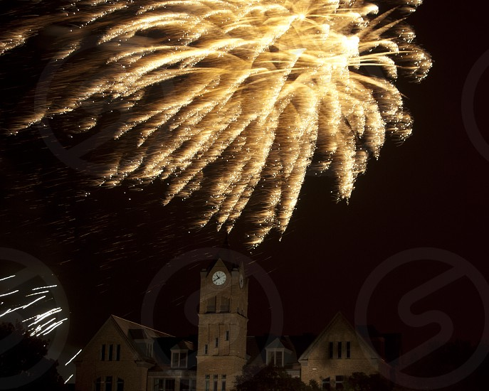 fireworks exploding behind a clock tower photo