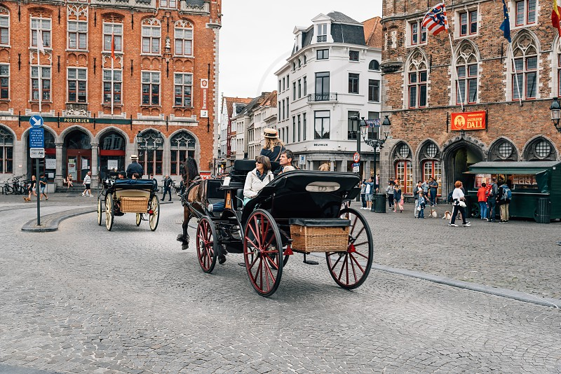 People in a horse carriadge in the entrance to Belfry of Bruges Belgium photo
