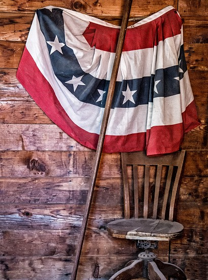 Nostalgic vintage looking photo of American flag hanging inside old western building. photo