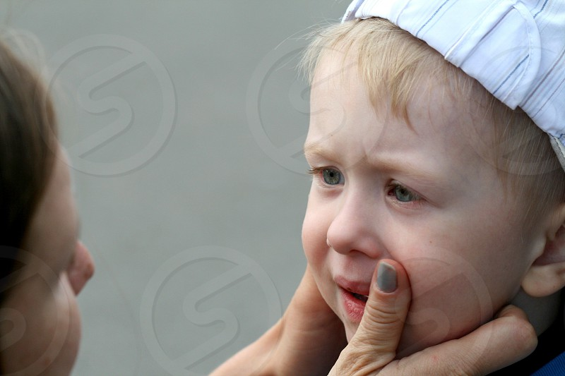 woman wiping the tears of boy photo