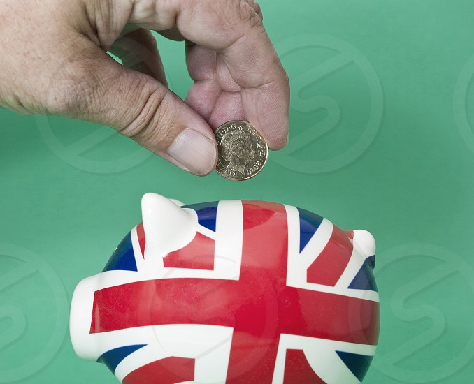 Saving British pounds. Depositing a pound coin in a piggy bank which sports a Union Jack logo photo