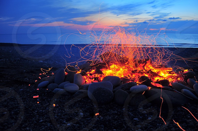 bonfire with fire by the beach under blue and teal skies photo