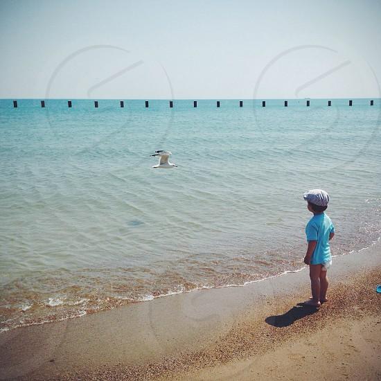 boy in green t shirt standing infront beach photo