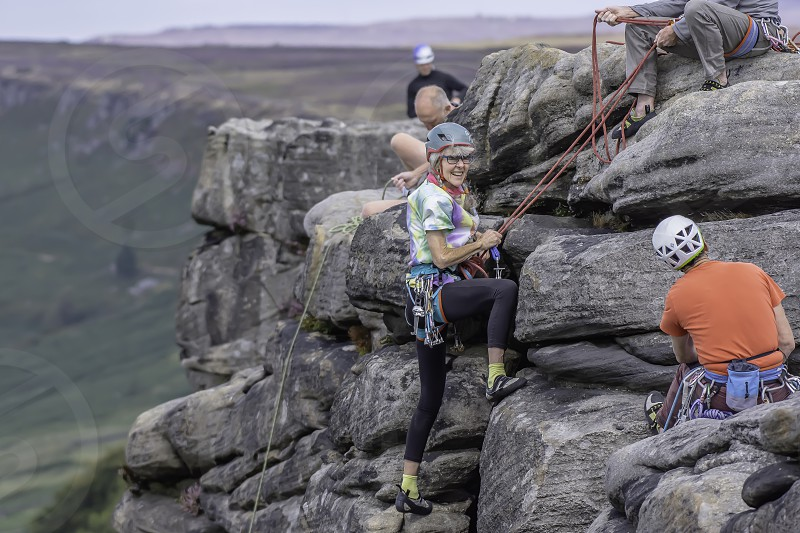 08.01.2018.Stanage EdgeDerbyshireUk.Active seniors.Mature woman-rock climber finishing climbing route with smile on her face.Group of climbers on cliff edge.Blurred landscape in background. photo