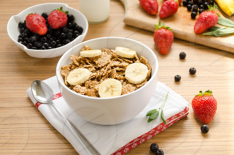Healthy breakfast with bowl of cereals (muesli) strawberry wild berries milk and banana on light wooden table. photo