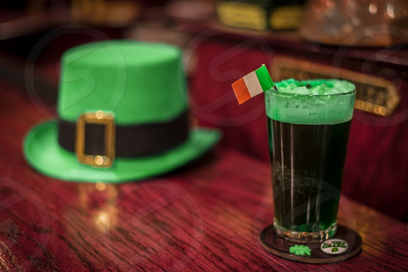 Glass of green beer with an Irish flag sitting on a coaster with a shamrock and button with a tap box and green leprechaun hat sitting on the bar in the background. photo
