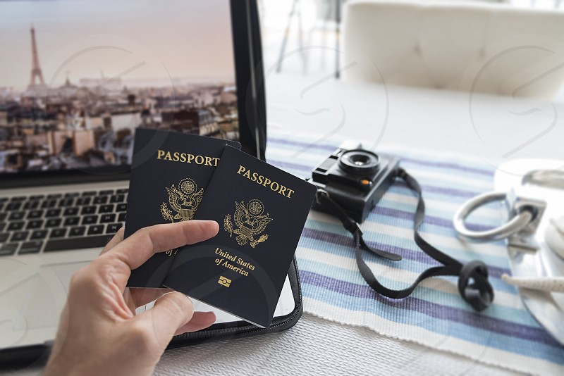 Point of view holding two passports with computer and camera. photo