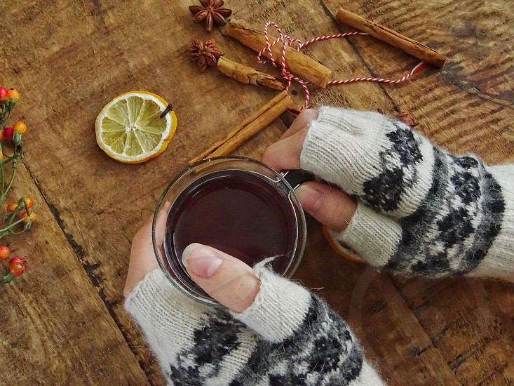 mittens hot drink tea decoration drink wooden background fingershands gloves wintertime winter season relaxing enjoy spices lemon slices cinnamon sticks cloves fruit star aniseanise photo