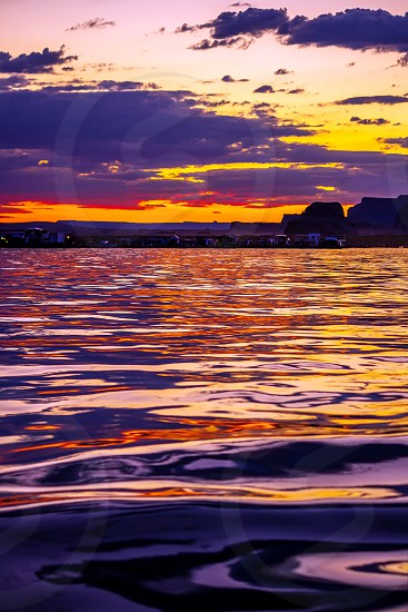 A row of houseboats docked in the shadows at Wahweap Marina at Last Chance in Lake Powell.  The sun is set and the last colorful light of day is painting the lake and sky around them. photo