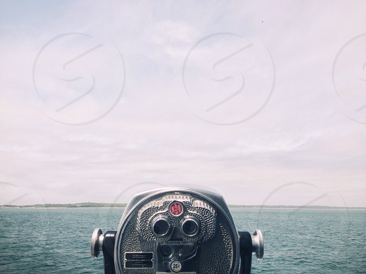 silver and black binoculars facing body of water photo