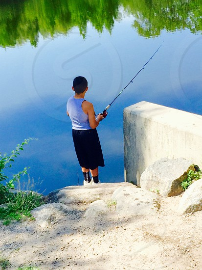 person in grey tank top and black knee level shorts fishing on a river next to a concrete stairs during daytime photo