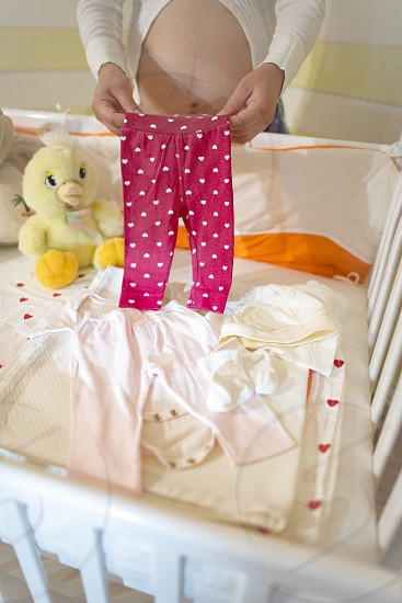 Pregnant women in a baby room. Preparing the room for the baby photo