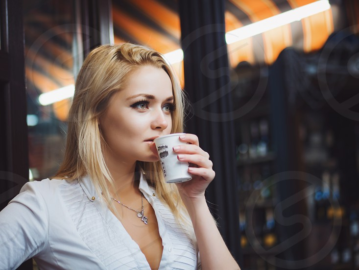 Portrait of young gorgeous female drinking tea and thoughtfully looking out of the coffee shop window while enjoying her leisure time alone nice business woman lunch in cafe during her work break photo