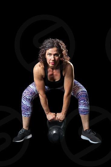 Intense image of a female weightlifter bending over to do a kettlebell dead lift. On a black background.  Path around the woman. photo