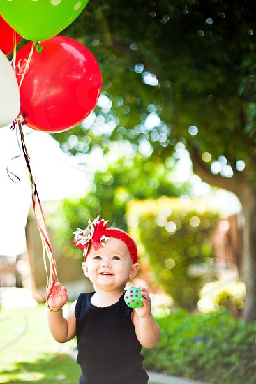 baby carrying balloons photo