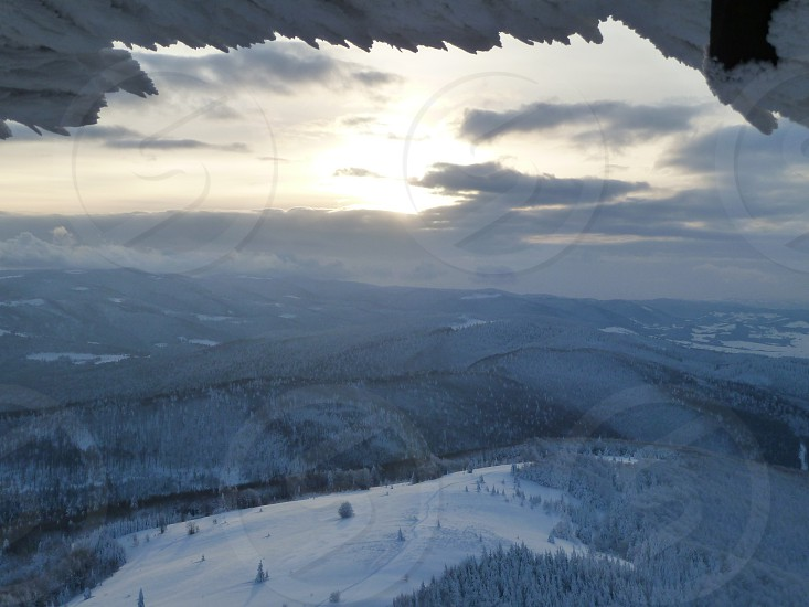 Cold winter sunset in mountains. Everything is covered with ice and snow ice-cold wind blows. photo