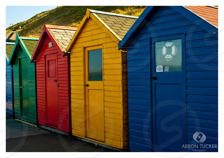 four assorted-color wooden sheds aligned photo